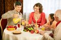 Traditional thanksgiving dinner portrait of happy family sitting at festive table and having Stock Photography