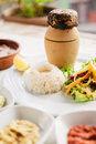 Traditional turkish pottery kebab on the table with rice and sal Royalty Free Stock Photo