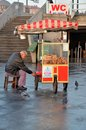 Traditional turkish pretzel seller prepares his pushcart bread early morning banks bosporus three penguins hoping crumbs walk Stock Photo