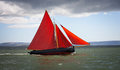 Traditional wooden boat with red sail. Royalty Free Stock Photo