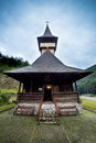 Traditional wooden church in the mountains against a cloudy sky Royalty Free Stock Photo