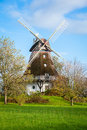 Traditional wooden windmill in a lush garden with four sails or blades turning the wind to generate power and energy for Stock Image