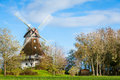 Traditional wooden windmill in a lush garden with four sails or blades turning the wind to generate power and energy for Royalty Free Stock Photography