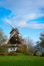 Traditional wooden windmill in a lush garden with four sails or blades turning the wind to generate power and energy for Royalty Free Stock Images