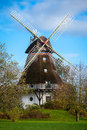 Traditional wooden windmill in a lush garden with four sails or blades turning the wind to generate power and energy for Stock Photos