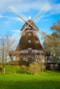 Traditional wooden windmill in a lush garden with four sails or blades turning the wind to generate power and energy for Stock Photo