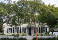 Traditional yellow home black shutters behind shade trees quiet southern street Stock Photos