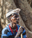 Traditionally dressed Hamar man with chewing stick in his mouth. Turmi, Omo Valley, Ethiopia