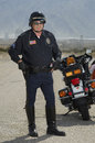 Traffic cop by motorcycle full length of on duty standing Stock Photos