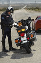 Traffic cop writing against motorcycle full length of a ticket on road Royalty Free Stock Photography