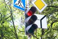 Traffic light and three road signs regulating the traffic. Royalty Free Stock Photo