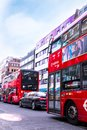 Traffic in London - two typical red buses with adverts and black mercedes, standing in traffic.