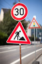 Traffic sign for roadworks ahead at the side of an urban road imposing a reduced speed limit Royalty Free Stock Image