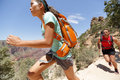 Trail runner cross country running grand canyon women in race in couple training working out together sprinting fast at speed in Stock Image