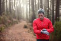 Trail runner looking at heart rate monitor watch man running in cold forest wearing hat and gloves male jogger running training in Stock Image