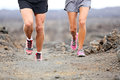 Trail running close up of runners shoes and legs athletes exercising cross country outside on rocks on volcano path Stock Photo
