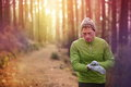 Trail running runner heart rate monitor watch looking at in forest wearing warm jacket sportswear hat and gloves male Stock Photography