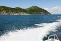 Trail on sea water surface behind boat against the backdrop of hilly terrain. Royalty Free Stock Photo