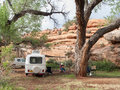 Trailer camp in a desert oasis truck and travel set up under large cottonwood tree next to red rock cliff with man playing guitar Royalty Free Stock Photos