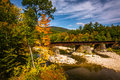 Train bridge over a river and autumn color near Bethel, Maine. Royalty Free Stock Photo