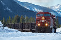 Train coming round the bend with canadian rockies in winter around background Royalty Free Stock Photos