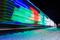 Train decorated with holiday lights arrives at station blue green Royalty Free Stock Image