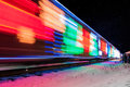 Train decorated with holiday lights arrives at station winter snow reflects Royalty Free Stock Images