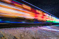 Train decorated with holiday lights blurs past orange Royalty Free Stock Photo