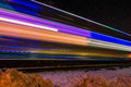 Train decorated with holiday lights blurs past purple Royalty Free Stock Photo