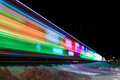 Train decorated with holiday lights leaves station winter snow reflects Royalty Free Stock Photo