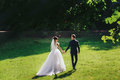 Train of a dress lies on the green lawn while bride holds groom` Royalty Free Stock Photo