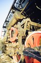 Train drive mechanism and red wheels of an old soviet steam locomotive. Vertical photography Royalty Free Stock Photo