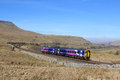 Train mallerstang and wild boar fell cumbria diesel multiple unit in northern rail franchise livery approaching ais gill summit on Stock Image