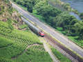 Train in moselle valley driving through vineyards amidst going from koblenz to trier Stock Photo