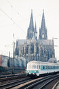 Train passing cologne cathedral germany europe leaving on railway track in front of monumental Stock Photos