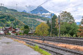 Train rails with a house and mountains in switzerland on a cloudy day Royalty Free Stock Photos