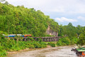 Train and railway beside cliff and river Stock Photo