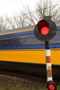 Train rushing past railway crossing blue yellow warning light at a Royalty Free Stock Images