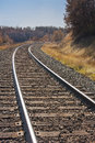 Train tracks curve through autumn grasses and trees Royalty Free Stock Photography