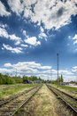 Train tracks lying between fields go off into daylight Stock Photos
