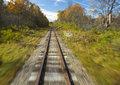 Train tracks in motion blur with autumn scene in background Stock Image