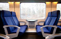 Train travel concept seats in interior of modern passenger wagon Stock Photos