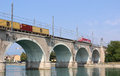 Train on viaduct river mincio peschiera del garda electric locomotive hauling a goods with containers crossing the railway over Royalty Free Stock Photo