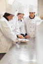 Trainees listening to the head chef in kitchen at culinary school Stock Photo