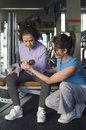 Trainer assistance senior woman in lifting dumbbell at gym full length of female women Royalty Free Stock Photography