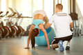 Trainer assisting woman on pilates ball Royalty Free Stock Photo