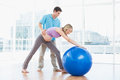Trainer exercising with blonde pregnant client and exercise ball in a studio Stock Photos