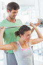 Trainer helping fit woman to lift barbell bench press male young women the in the gym Royalty Free Stock Photography