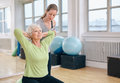 Trainer helping senior woman exercising women doing light pilates workout for back muscles with coach assistance women at gym Royalty Free Stock Images