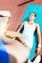 Trainer helping to ease the strain young beautiful sportswoman having a and being stretched by Stock Images